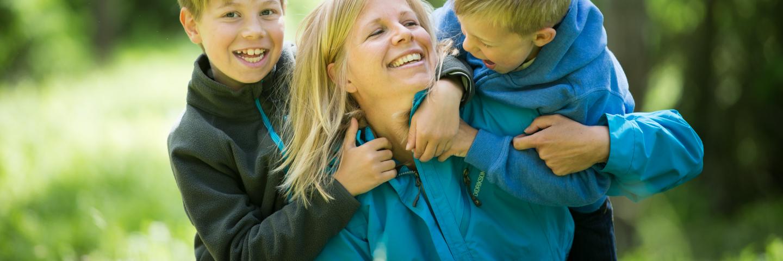 Mammabusar och leker med två pojkar i skogenMum playing with two boys in the forest