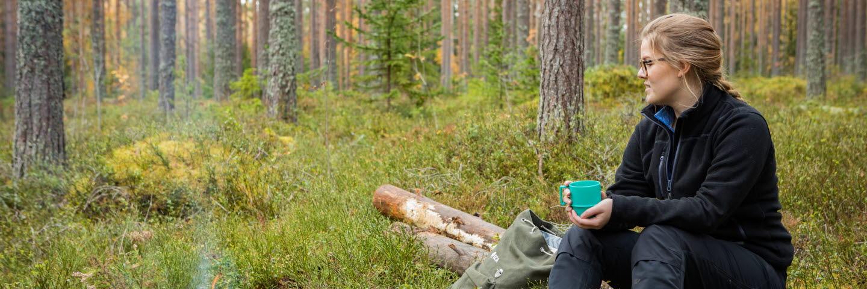 Kvinna vistas i skogen som rekreation.